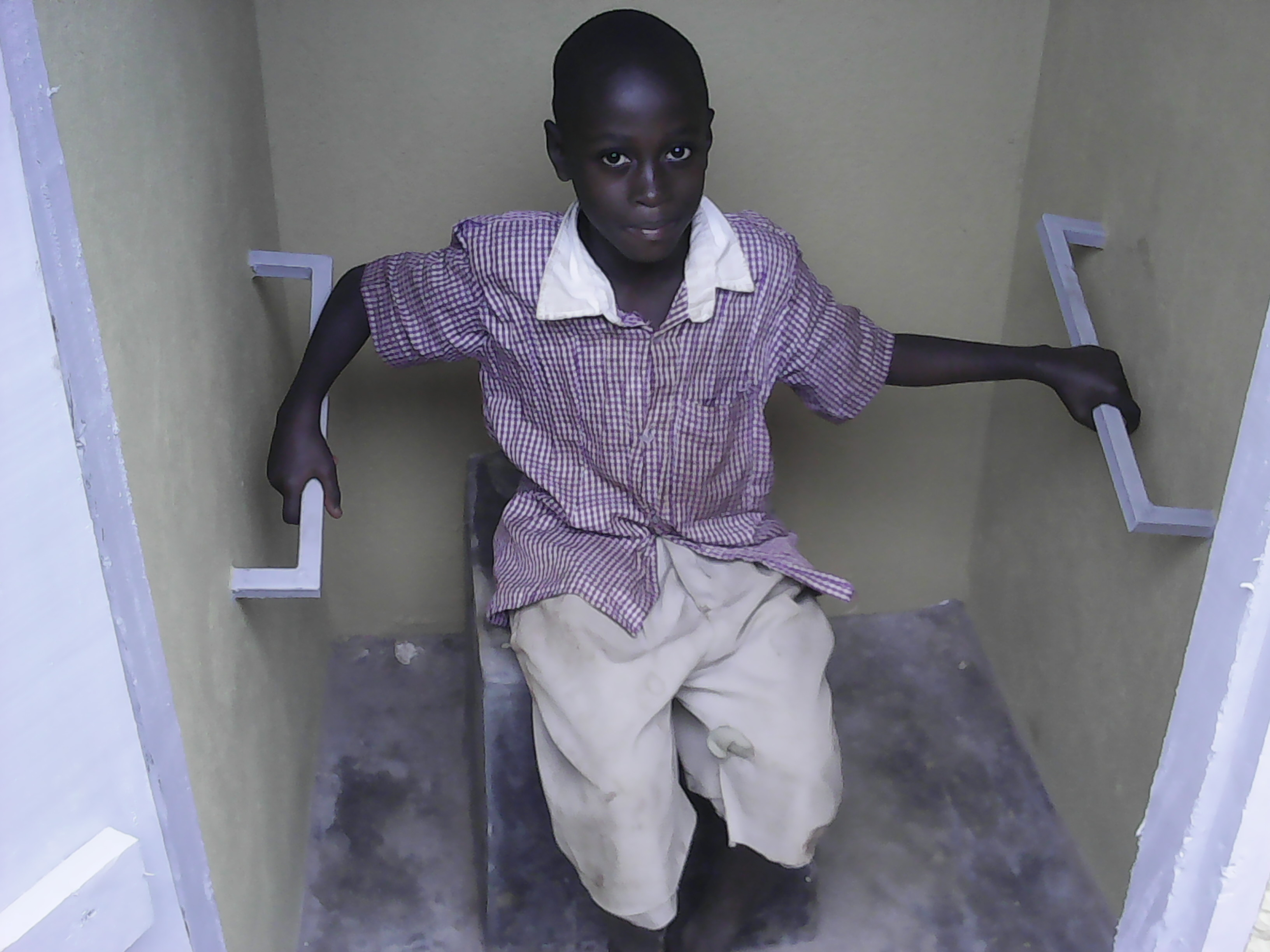 John living with disabilities tries on sensitive toilets constructed by CESA-Uganda